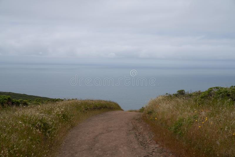 Dirt path dipping below view leading to ocean water, sense of unknown stock photos