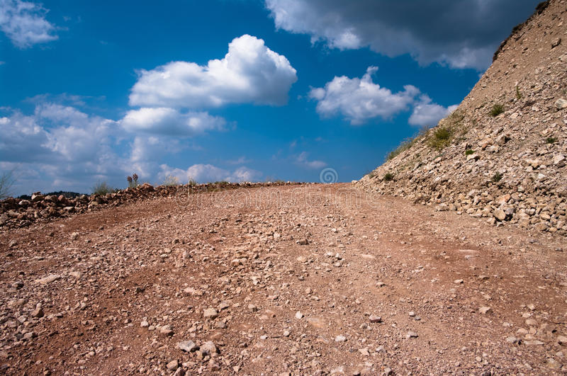 Dirt road. Of rocky ground on background clouds in blue sky royalty free stock image