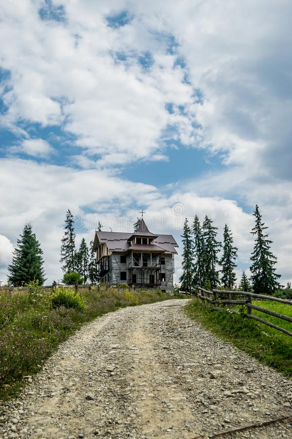 Dirt road and abandoned wooden house stock photo