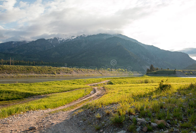 Dirt road along Snake River and Central Rocky Mountains under cumulus cloud sky in Alpine Wyoming stock photography