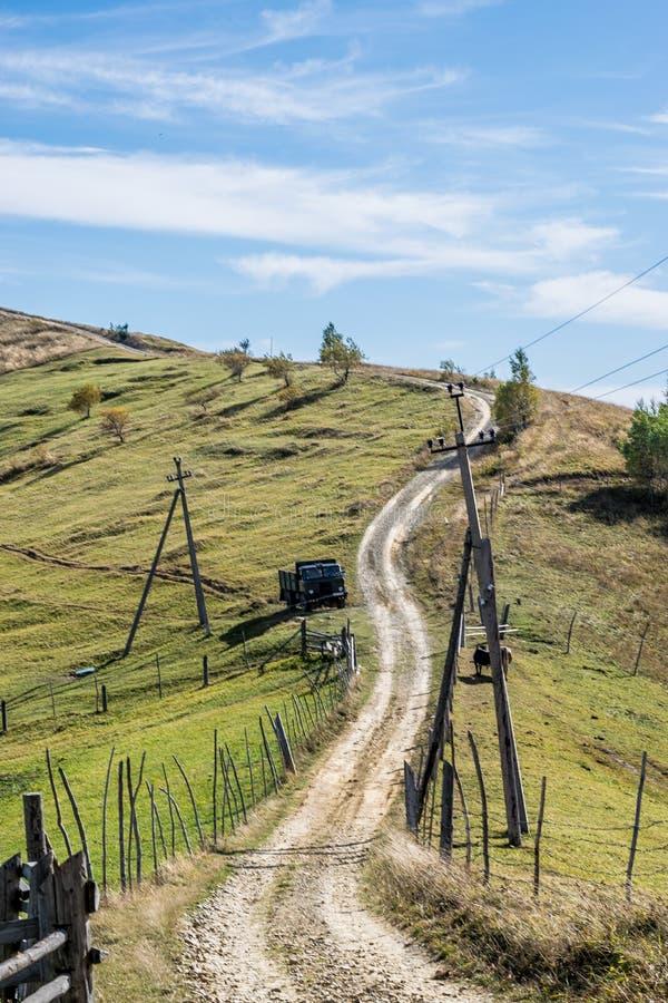 Dirt road through the Carpathian hills and Soviet GAZ 66 truck stock photography
