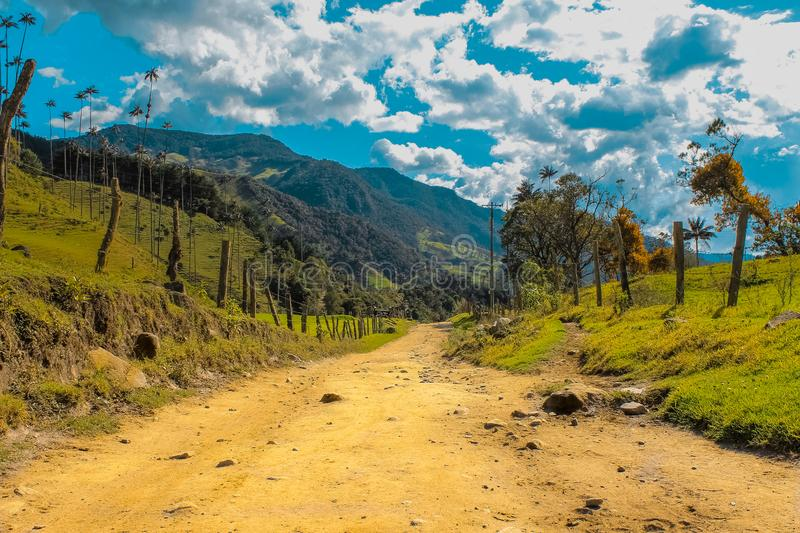 Dirt road in Colombia. Old, blue, sky, mountain, trees, grass, clouds, nopeople, nature, natural stock images