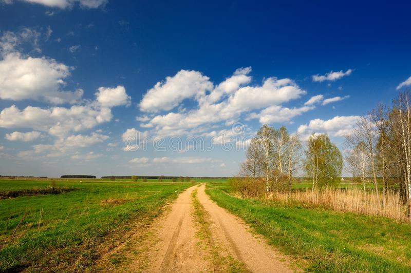 Dirt Road in Countryside. A dirt road in the countryside with green grass and trees under a bright blue sky stock photos