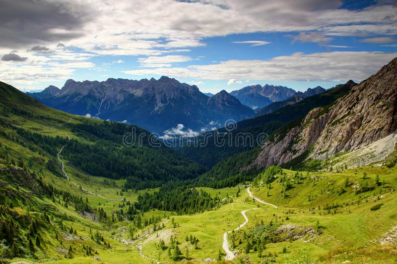 Meadows and jagged peaks of Carnic Alps and Dolomiti Pesarine. Dirt road curving on sunlit meadow in Forcella Dignas pass in Alpi Carniche with Terza Siera in royalty free stock photos