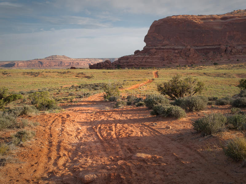 Dirt road in desert. A dirt road leads through desert sage brush country to red sand stone cliffs in the distance near Canyon Lands National Monument, Utah stock photos