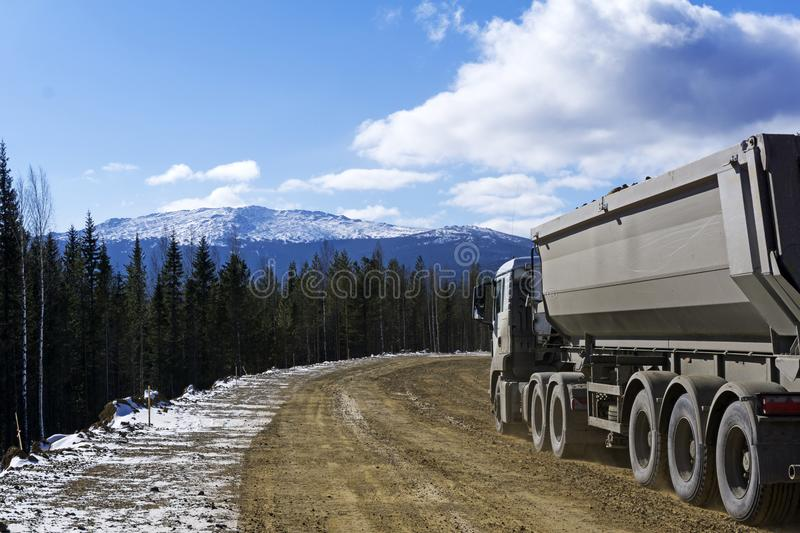 Dirt road with a dump truck in the northern highlands. Repaired dirt road with a dump truck in the northern mountainous woodland in winter royalty free stock image