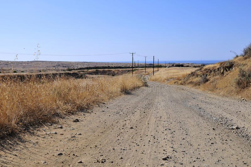 Dirt Road. Heading surrounded by dry fields heading towards the sea royalty free stock photos