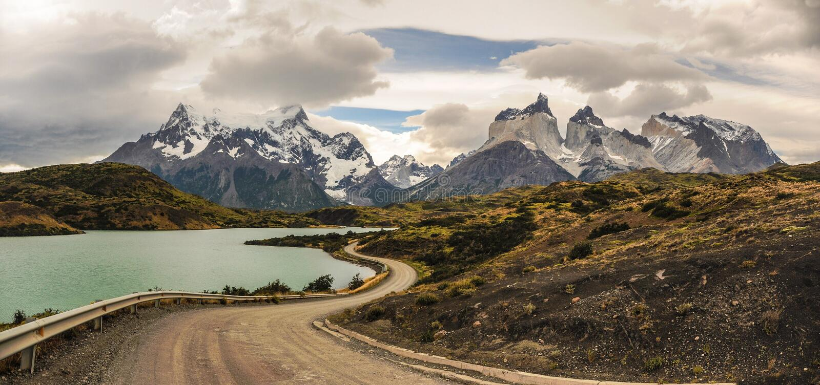 Dirt road leading around the lake to stunning Cuernos del Paine in Patagonia. Torres del Paine National Park, Patagonia, Chile the stock photos
