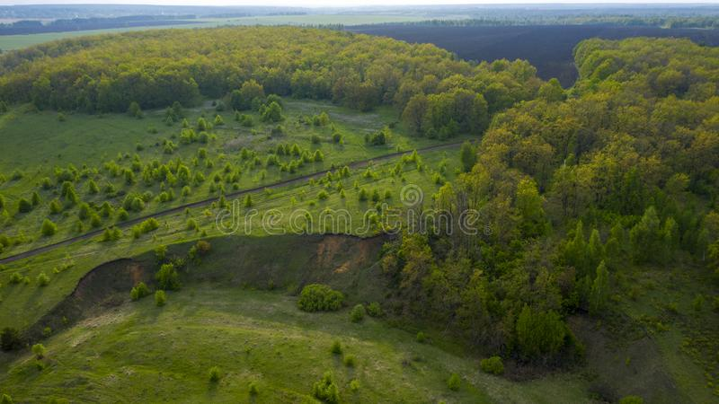 Dirt road through meadows, forests, fields from a bird`s-eye view, with a quadrocopter royalty free stock images
