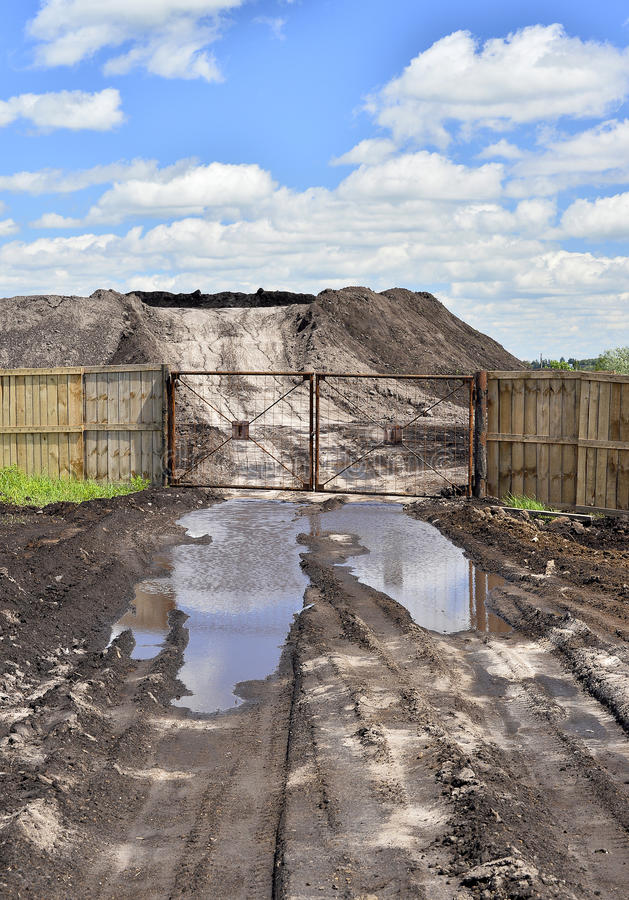 Dirt road, a pool and a lot of stored in the open air ground for a closed fence stock photo