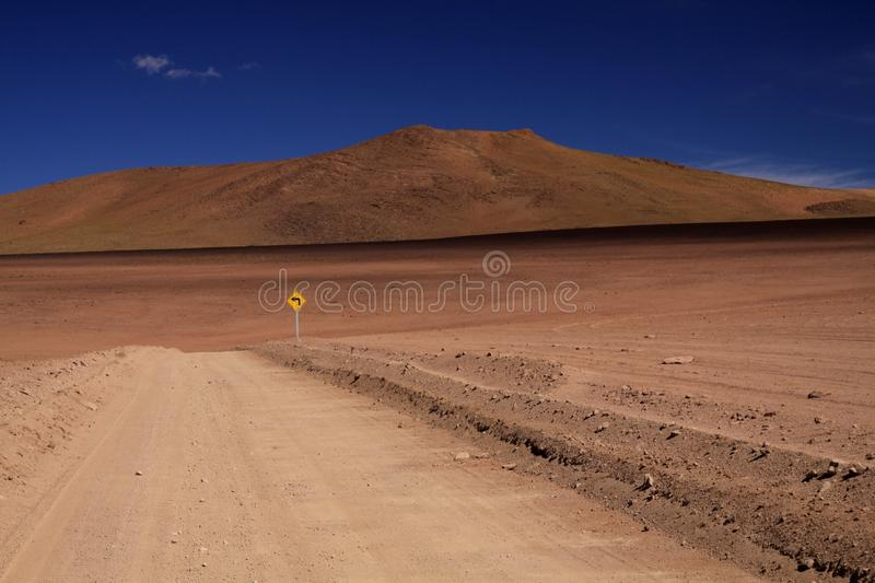 Dirt road through red wasteland contrasting with deep blue cloudless sky,  lost yellow sign showing left direction - stock images