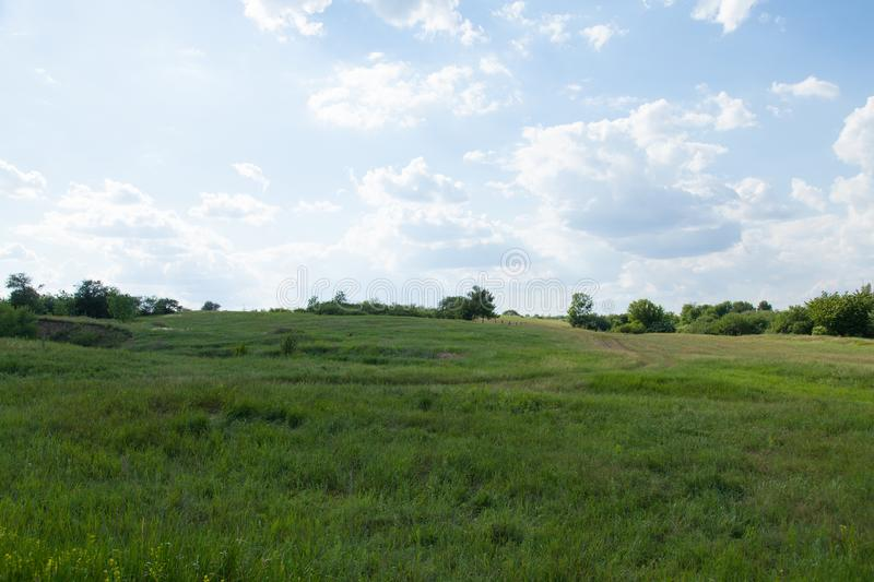 Dirt road rural on a hill in the grass horizon and cloudy blue t royalty free stock images