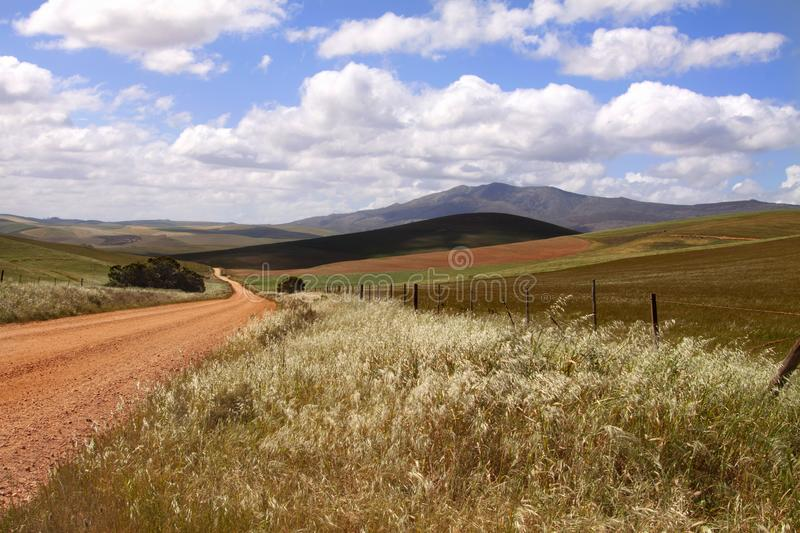 A dirt road in rural Kwazulu Natal Midlands, South Africa. Cloudy sky royalty free stock images