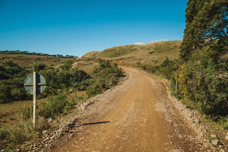 Dirt road on rural lowlands with dry hills stock images