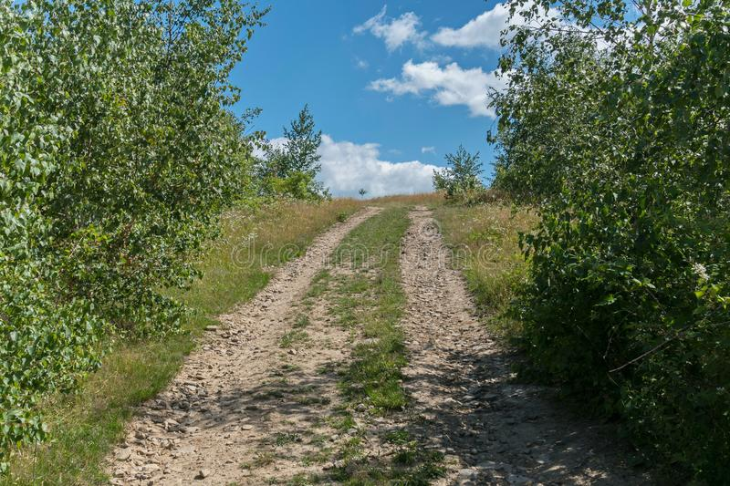 A dirt road strewn with rubble going to the hill between bushes with a blue sky in the distance with clouds visible in royalty free stock photography