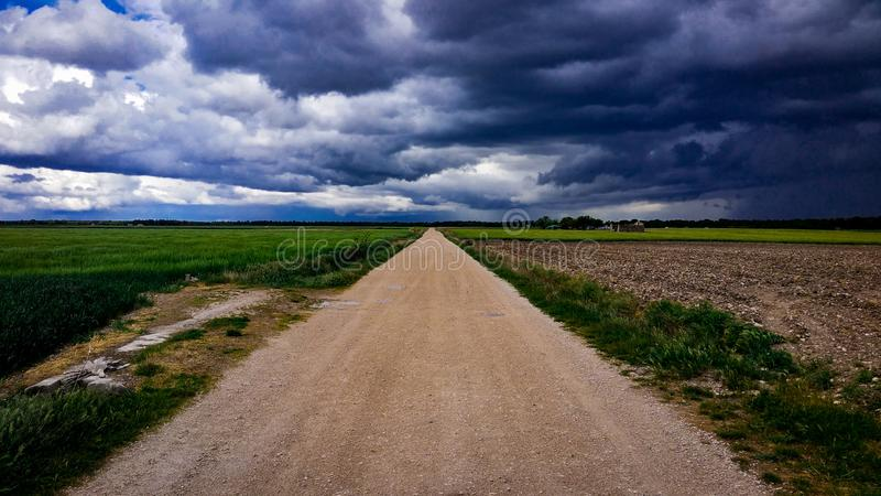 Dirt Road Surrounded With Green Field Under Cloudy Sky stock image