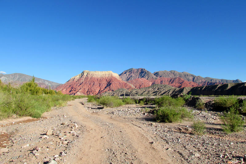 Dirt road to red mountain. Red color mountainson sunny day with blue sky. Dirt road to red mountain in countryside. Red cliff far away stock photography