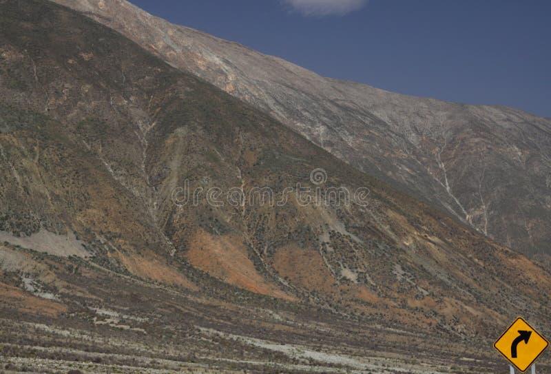 Dirt road to salt flat plateau near San Pedro de Atacama with mountain face scenery, Chile. Yellow  sign showing right. Dirt road to salt flat plateau near San royalty free stock images