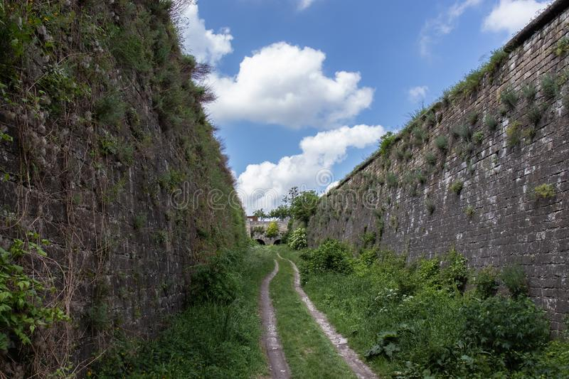 Dirt road between two stone ramparts. Dirt road leading to the castle between two stone ramparts under a cloudy sky stock photos