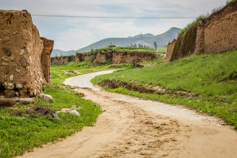 Smooth dirt road winds up a small hill around a mud wall in rural China. A dirt road winds up a small hill around a mud wall in rural China royalty free stock photo