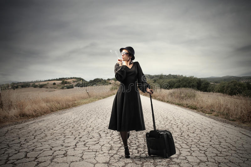 Dirt road. Woman walking with suitcase by a dirt road stock photography