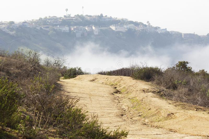 Dirth path at the top of trail in Laguna Beach. Dirt path at Aliso and Woods Canyon Wilderness Park overlooking a neighborhood on another mountain peak. Hiking royalty free stock photos