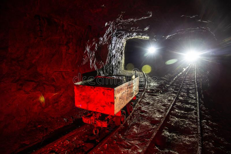 Dirty abandoned uranium mine with rusty rail and trolley.  stock photo