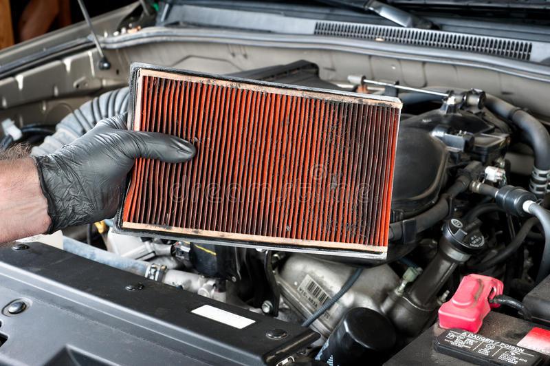 Dirty air filter. An auto mechanic wearing protective work gloves holds a dirty, clogged air filter over a car engine during general auto maintenance royalty free stock photography