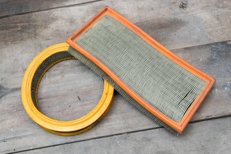 Dirty använde filter för luft för kabinbilen på träbakgrund royaltyfri bild