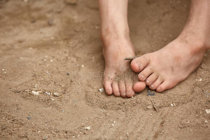 Dirty bare feet of poor little girl, selective focus, shallow depth of field. stock photo