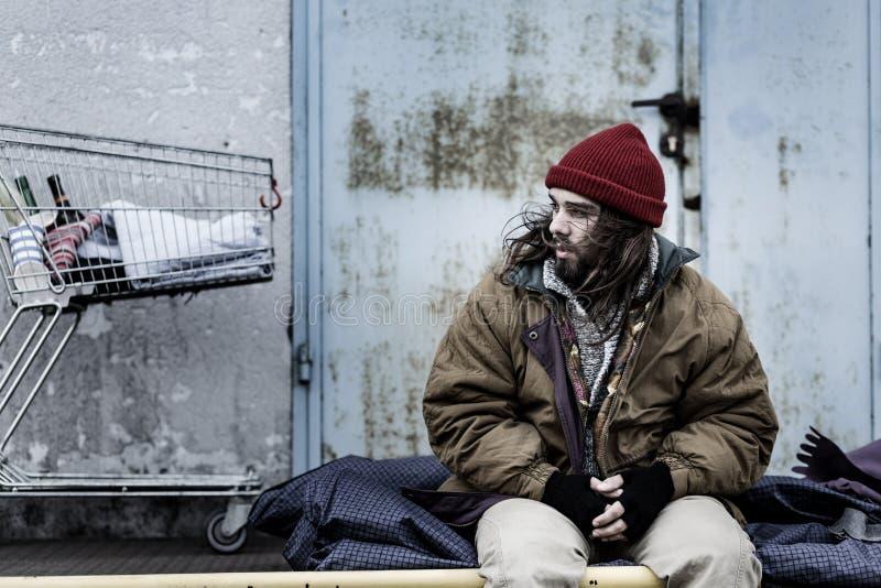 Dirty beggar sitting on night-bag stock photo