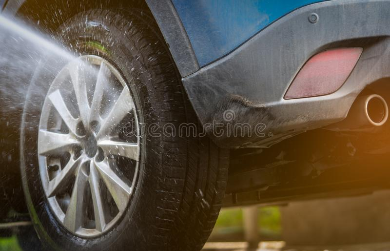 Dirty blue SUV car are washing with water. Car care service business concept. Car cleaning with high pressure water spray. Car stock photo