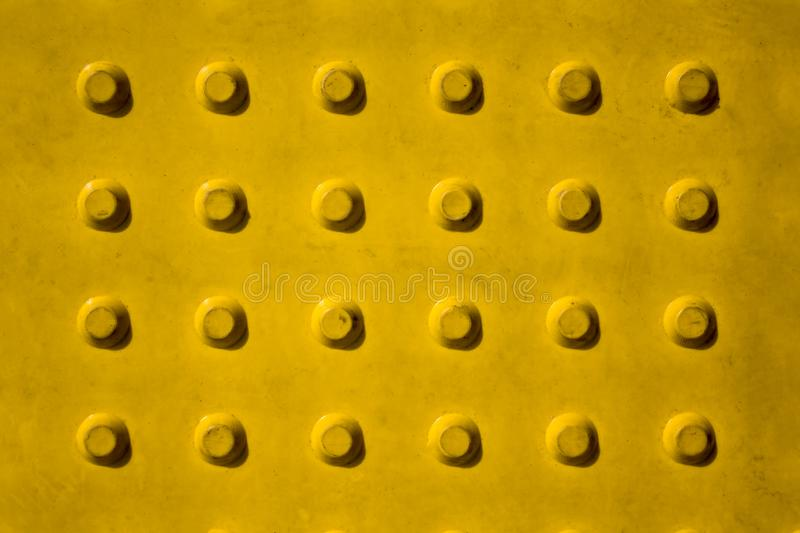 Dirty bright yellow metal wall with large rivets and shadows. rough surface texture royalty free stock images