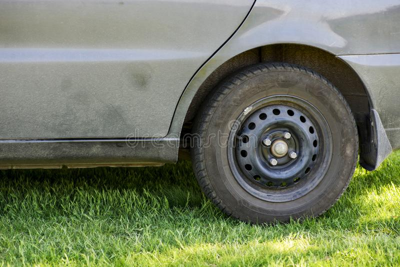 The dirty car, the car costs on a green grass in the field. The fender close up splodgy with dirt stock photos