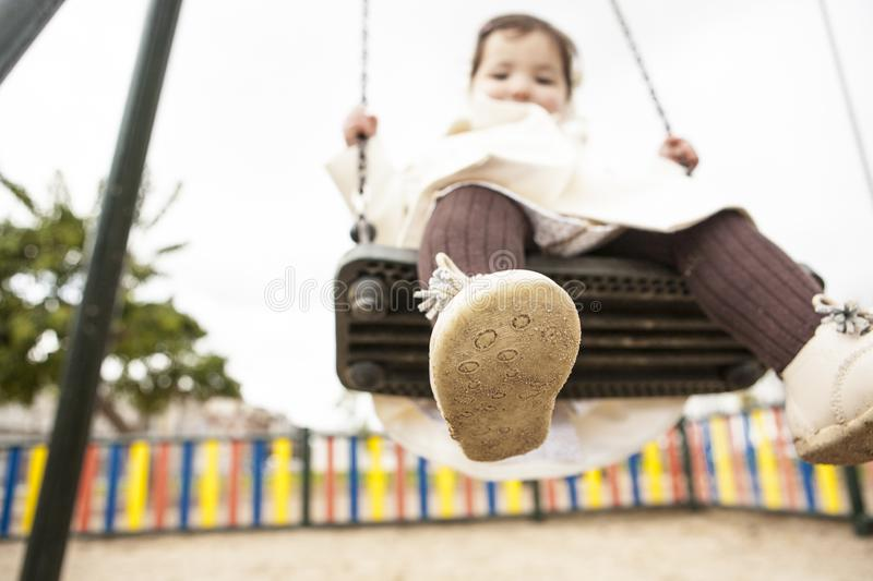 Dirty children shoes concept. Happy baby girl having fun on a swing on winter. Dirty children shoes concept stock images