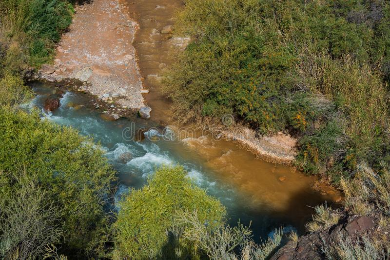Dirty and clean water. Confluence of dirty and clean rivers in Kyrgyzstan royalty free stock image