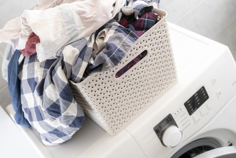Dirty clothes in plastic basket at a laundry lay on washing mashine and table b royalty free stock images