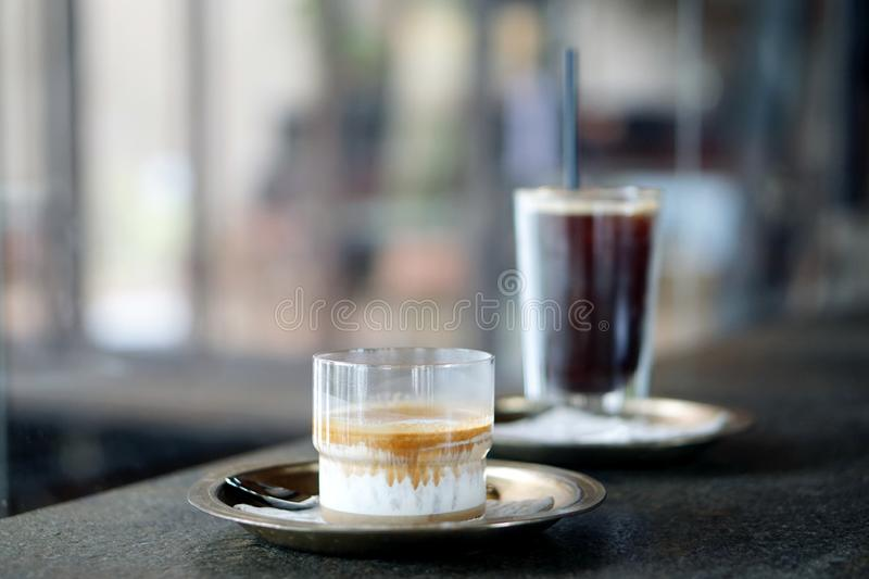 Dirty Coffee - A glass of espresso shot mixed with cold fresh milk served with Iced Americao on blurred background and copy space. Perfect drink for summer stock photography