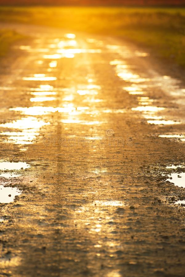 Dirty countryside road at sunset -on the road off road concept stock photography