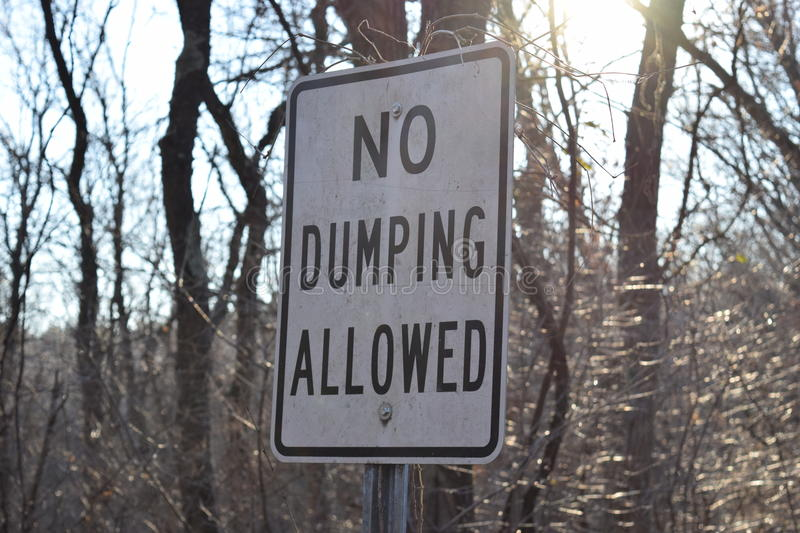 Dirty Cracked No Dumping Allowed Street Sign.  stock photography