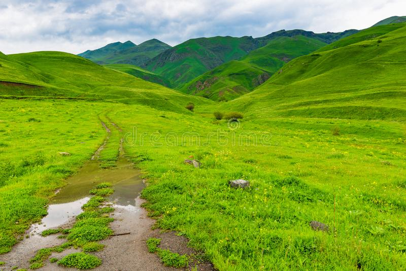 Dirty dirt road leading to the mountains. Armenian landscape stock photos