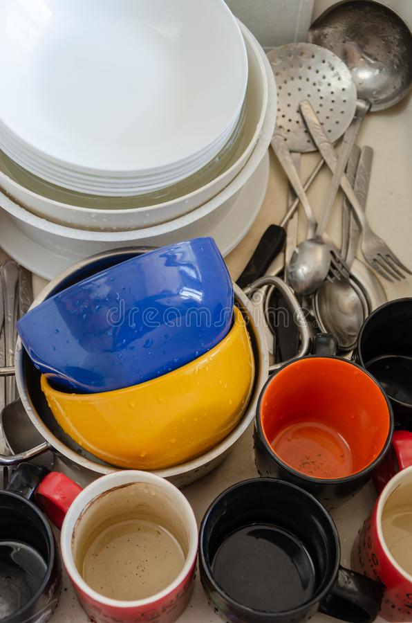 Dirty dishes in a ceramic kitchen sink. Unwashed plates, mugs and cutlery. Top view stock photo