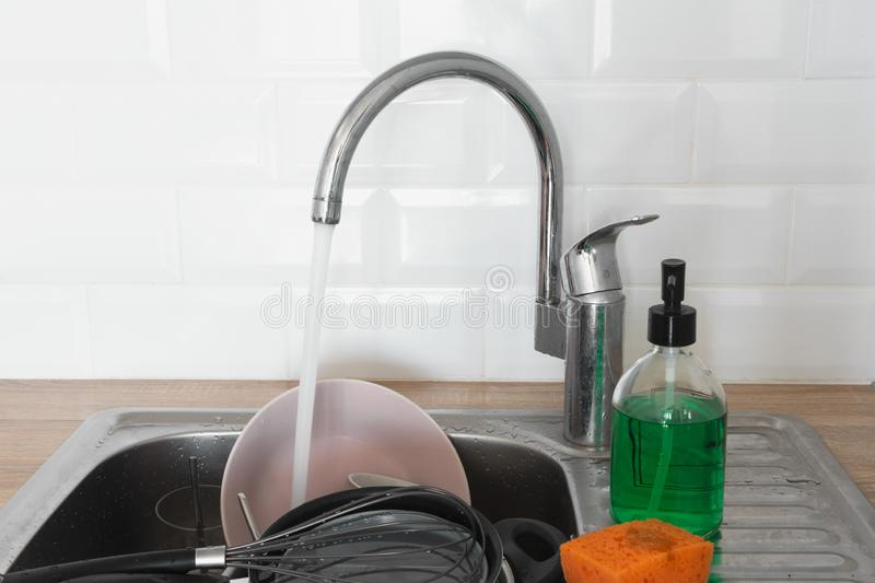 Dirty dishes in metal kitchen sink running tap water. Needing washing-up. Cleaning chores. Professional service cleaning stock photo