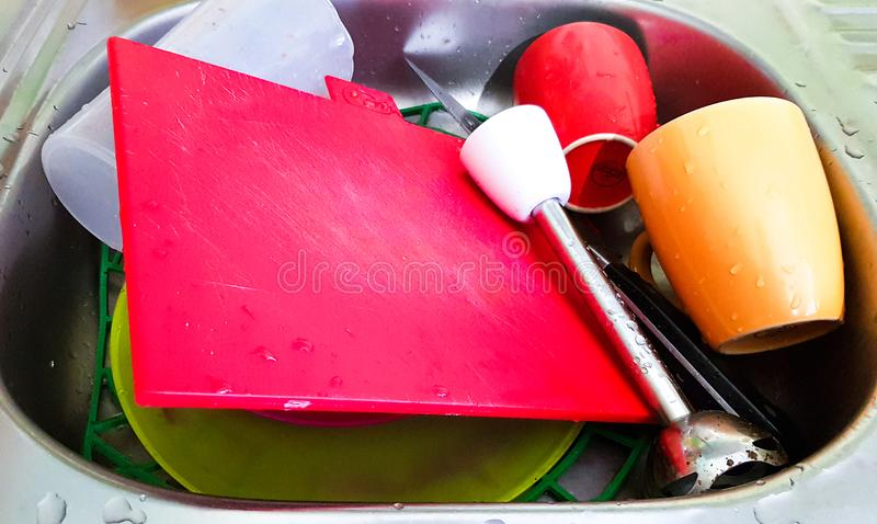 Dirty dishes in the sink. Unwashed utensils and utensils in the kitchen sink. The concept of washing dishes stock photos