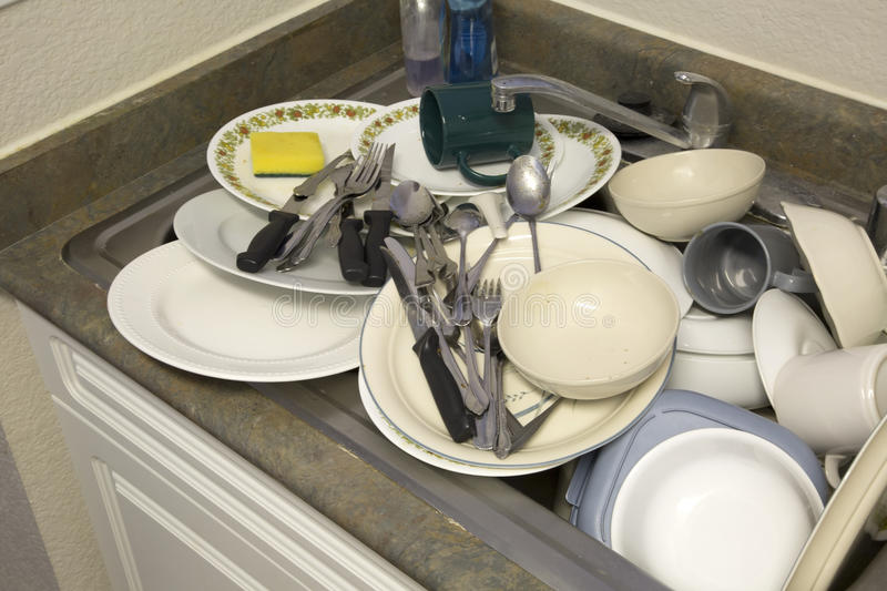 Dirty dishware in the sink. Dishware cleaning in the sink royalty free stock image