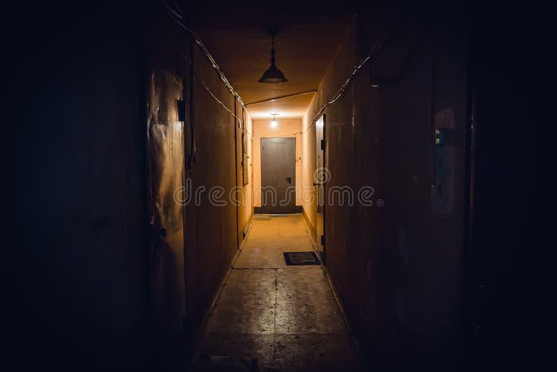 Dirty empty dark corridor in apartment building, doors, lighting lamps stock images