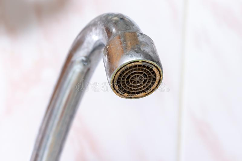 Dirty faucet aerator with limescale, calcified water tap with lime scale in kitchen, close up.  royalty free stock photo