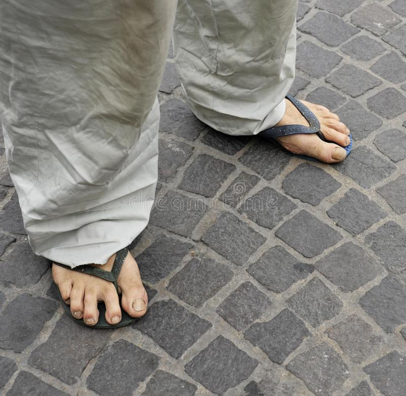 Dirty feet of a man wearing flip flops on the old stone floor. Bologna, Italy royalty free stock images