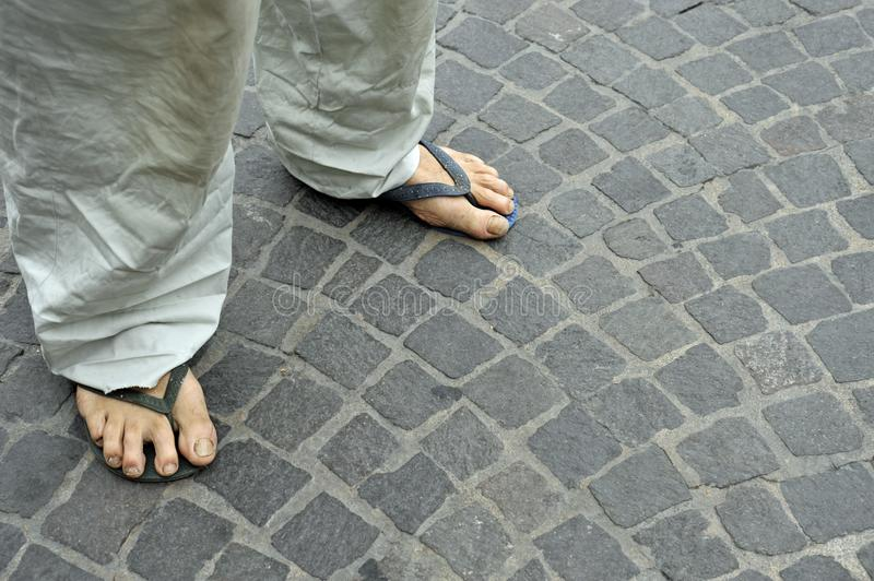 Dirty feet of a man wearing flip flops on the old stone floor. Bologna, Italy stock image