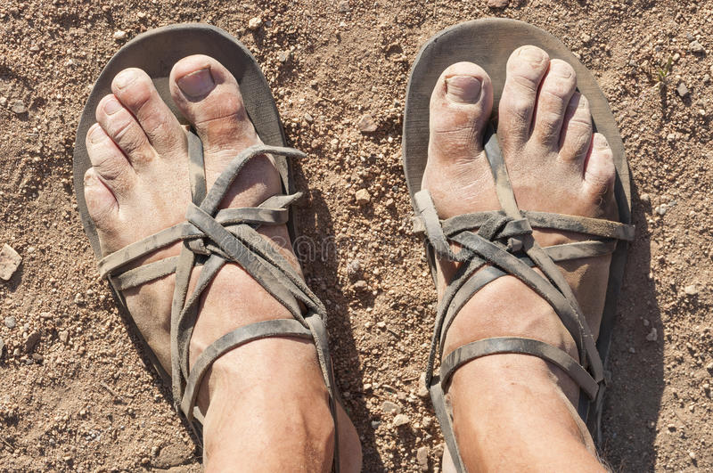 Dirty feet in sandals. Closeup POV of dusty male feet in traditional rustic leather strap sandals standing on dry barren ground royalty free stock photo